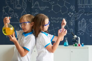 Kid of goggles standing back to back with flasks of reagent in hands