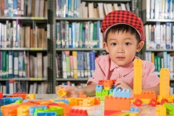 boy-playing-with-plastic-blocks-library-room-school