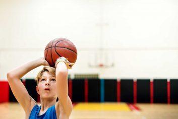 young-caucasian-boy-playing-shooting-basketball-stadium